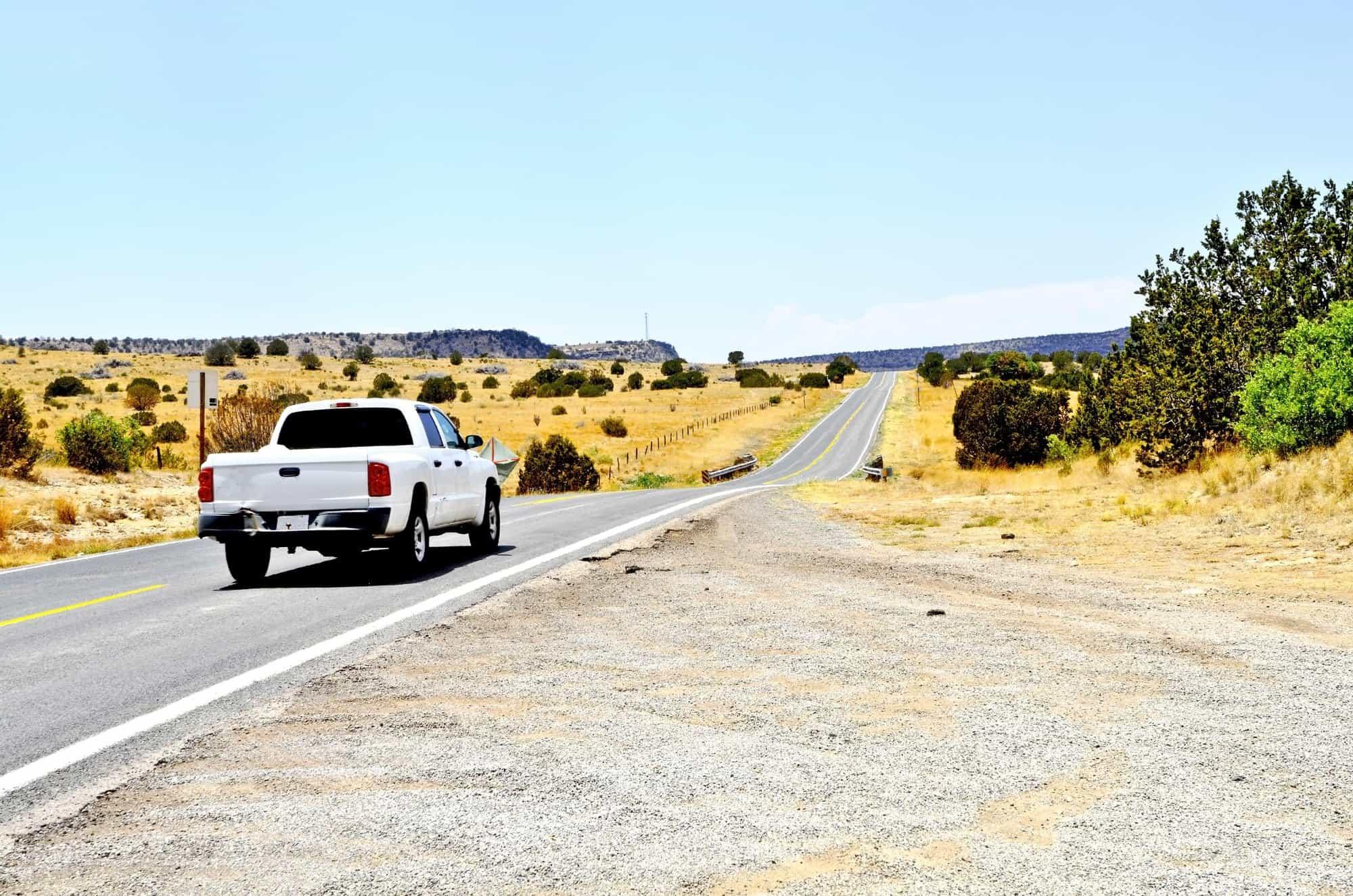 White work pickup truck driving down road