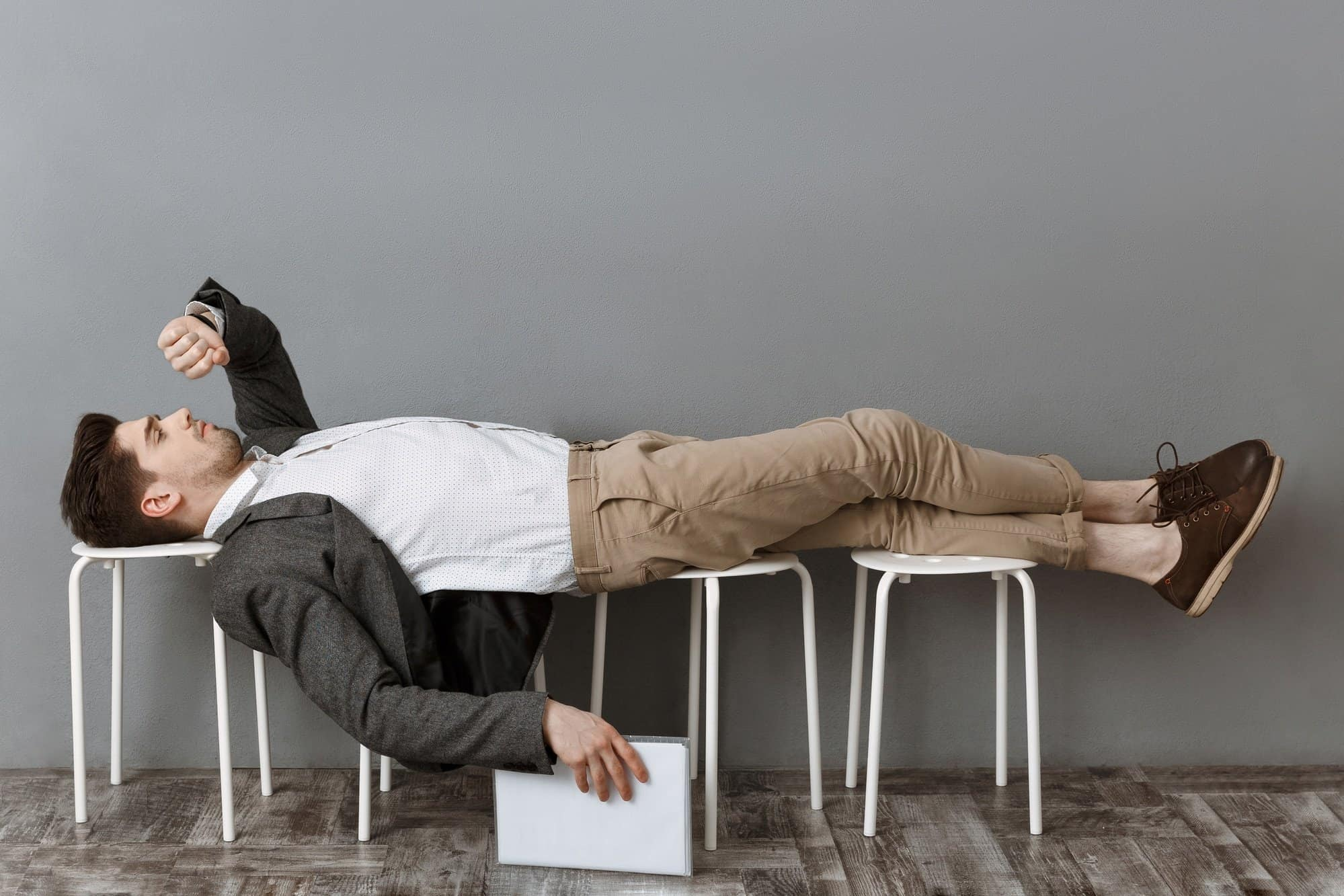 Employee with documents checking time while lying on chairs waiting for work
