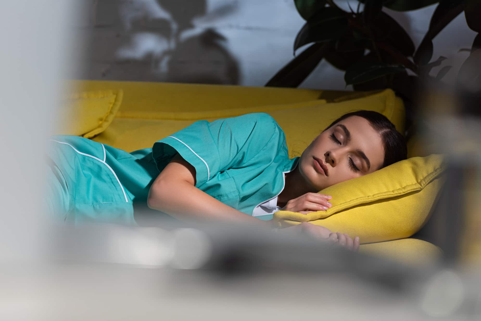 Selective focus of nurse in uniform sleeping on yellow sofa during night shift