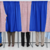 people in voting booths with only their legs showing