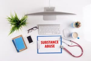 Office desk with SUBSTANCE ABUSE paperwork and other objects around, top view