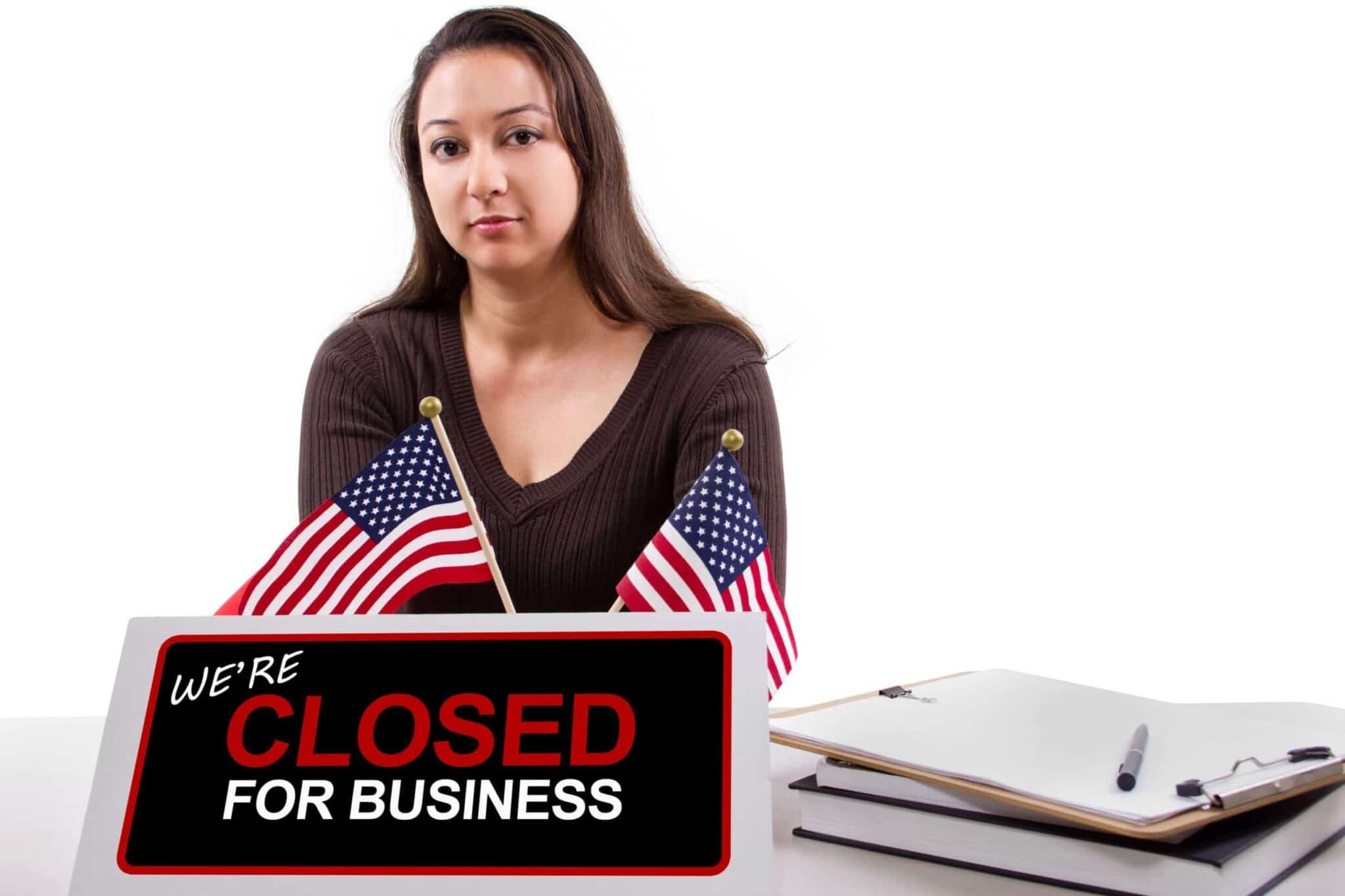 woman with a desk sign showing closed for business