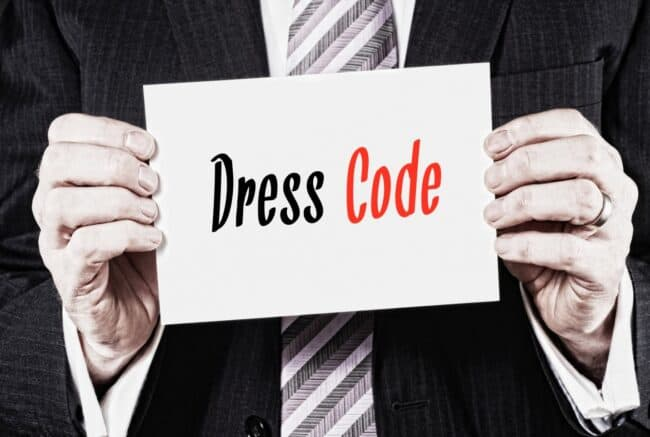 Man holding a card with dress code written on it