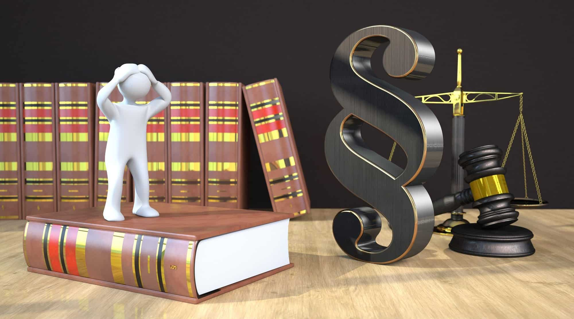 Desperate Manikin Desperate manikin on the law book on the table with a paragraph, scale and gavel. 3d illustration.Desperate manikin on the law book on the table with a paragraph, scale and gavel.
