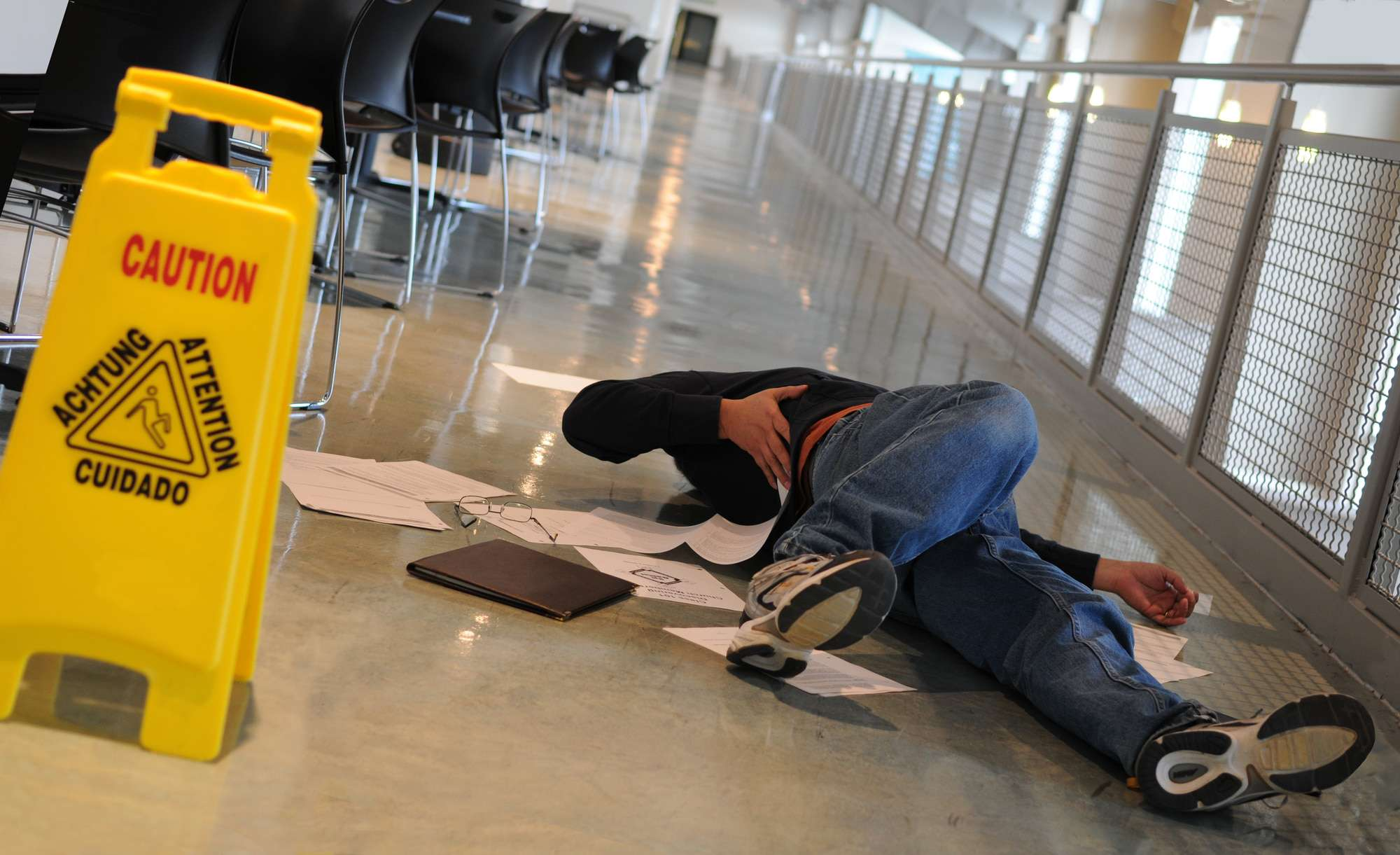 A man who slipped on a wet floor beside a bright yellow caution sign holds his back in pain