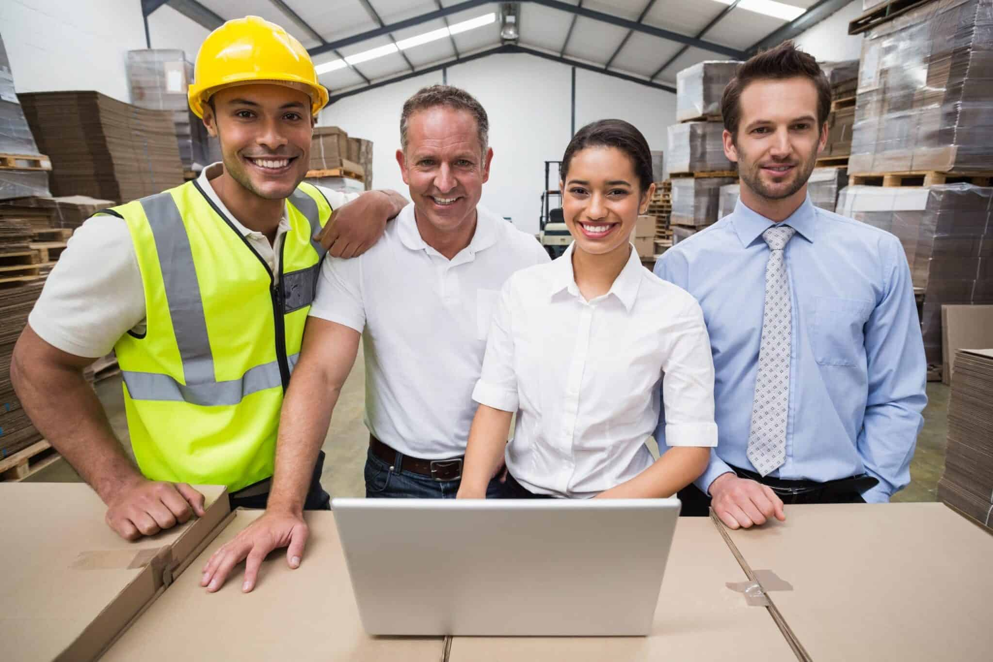 Warehouse managers and workers smiling at a camera in a large warehouse