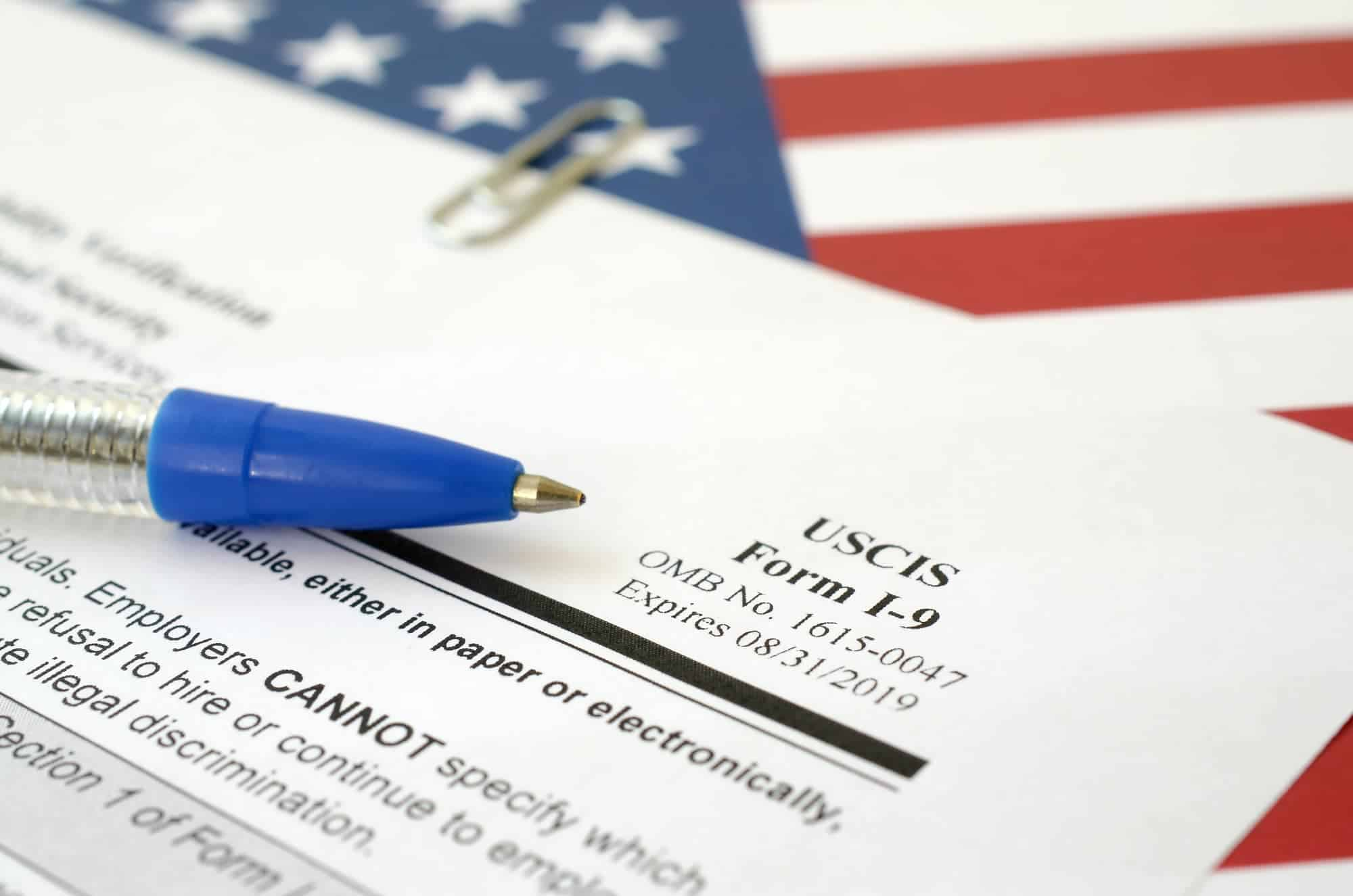 I-9 Employment Eligibility Verification blank form lies on United States flag with blue pen from Department of Homeland Security close up