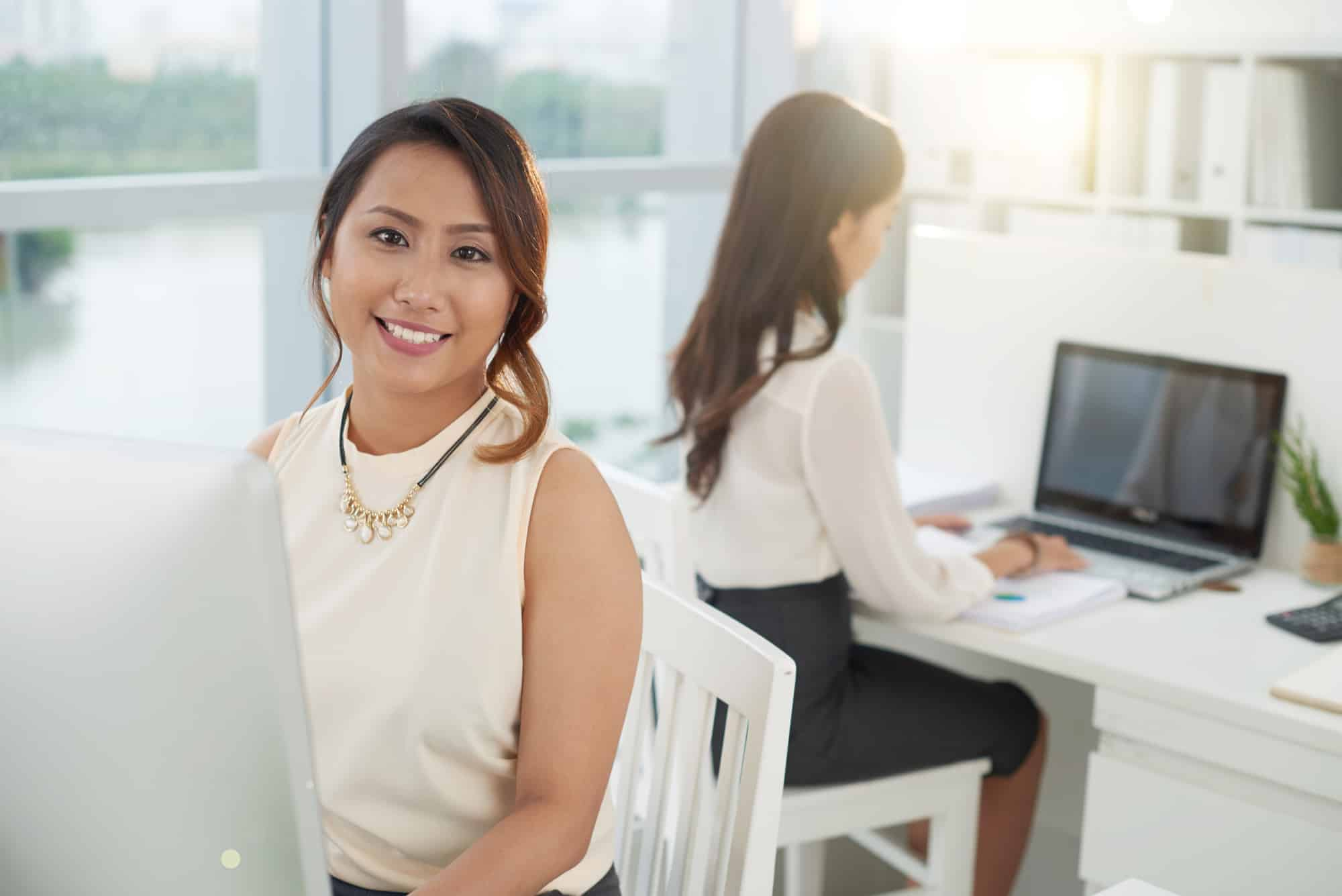 Smiling businesswoman sitting at her workplace and work